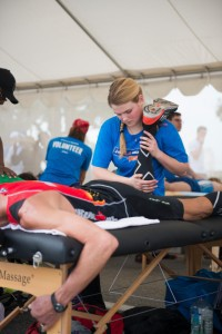 A runner who moments earlier finished the Los Angeles Marathon lies on his front in a volunteer massage tent to receive a massage. Santa Monica, California